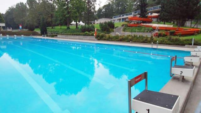 Ein Schwimmbecken mit einer roten Rutschbahn im Hintergrund.