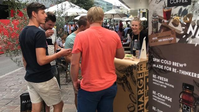 Junge Männer probieren das kalte Getränk an einem Stand.