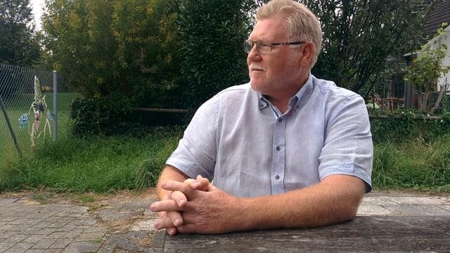 Anton Lässer ist stämmig, in einem blauen Kurzarmhemd, er sitzt am Holztisch und schaut etwas nachdenklich auf die Trainingswiese in Diepoldsau.