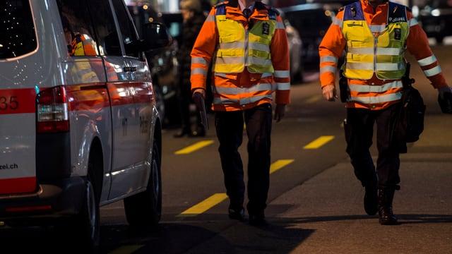 Ein Polizeiauto steht nachts am Strassenrand. Daneben laufen zwei Polizisten in gelber Warnweste.