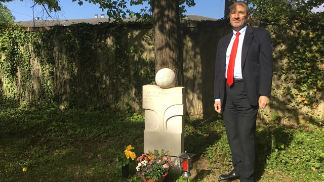 Ein Mann vor einem Grabstein