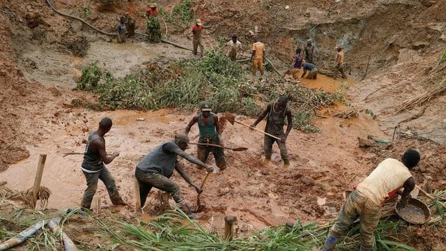 Arbeiter stehen im Wasser mit Schaufeln in einer Mine.