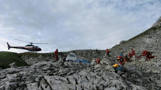 Helikopter und Personen in einer gebirgigen, steinigen Landschaft.