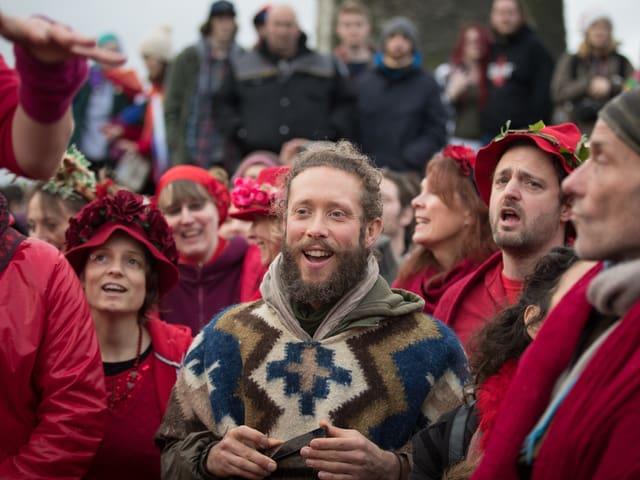 Eine Gruppe von Leuten in roten Kleidern singt