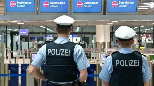 Zwei Polizisten stehen vor einer geschlossenen Sicherheitskontrolle am Frankfurter Flughafen.