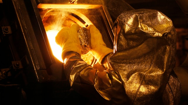 Ein Giesser im Schutzanzug wirft einen Silberklumpen ins geschmolzene Gold.