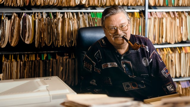 Al Imfeld mit Pfeife in seinem Büro.