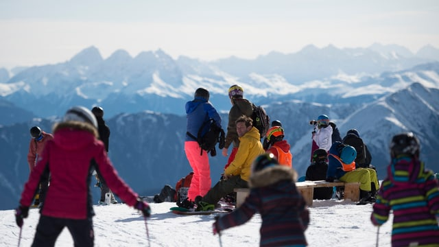 Persunas che van cun skis e snowboard sin il Crap Sogn Gion sur Laax.
