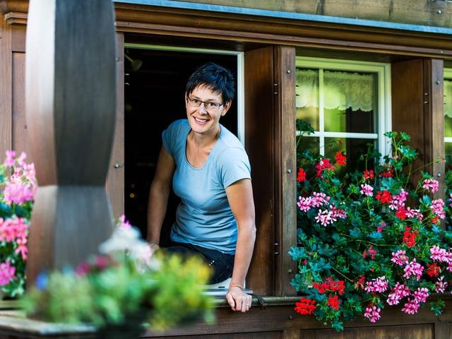 Theresia Hollenstein schaut aus dem Fenster, welches mit Geranien geschmückt ist.