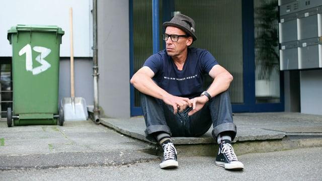 Ein Mann mit Hut und Brille sitzt vor einem Hauseingang auf dem Boden.