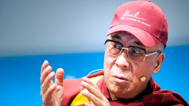Der Dalai Lama kleidete sich für seinen Auftritt an der Uni Lausanne mit der Schirmmütze der Hochschule.