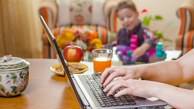Frau am Computer, im Hintergrund ein spielendes Kind