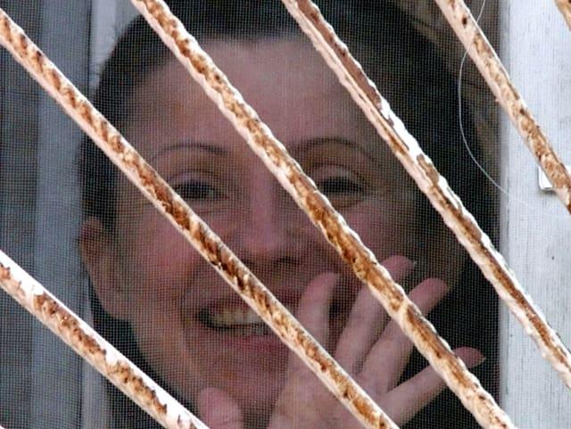 Timoschenko winkt im März 2001 aus einem vergitterten Fenster eines Spitales, in dem sie festgehalten wird.
