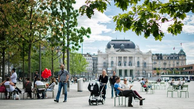 Blick auf den Sechseläutenplatz mit dem Opernhaus im Hintegrund und einer Bauminsel links im Bild.