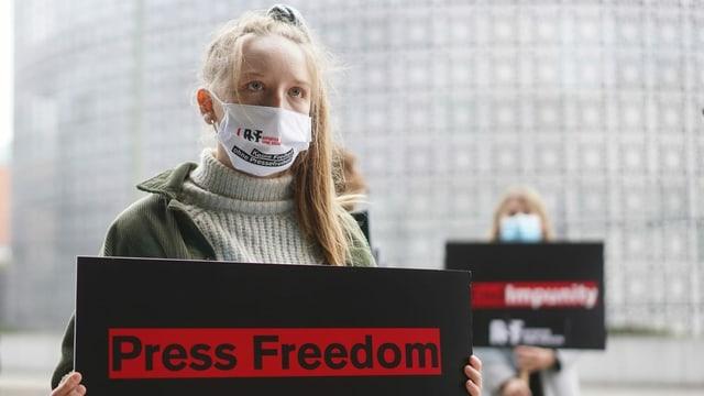purtret d'ina giuvna dunna che tegna in placat enta maun durant ina demonstraziun, quel ha scrit si per englais «press freedom» «libertad da pressa».