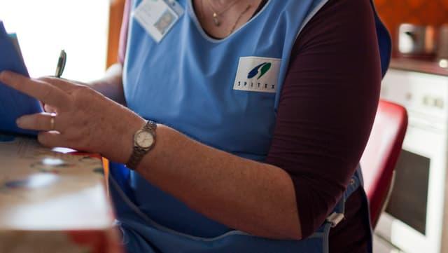 Eine Person in einer Spitex-Schürze trägt in ein Dokument etwas ein.
