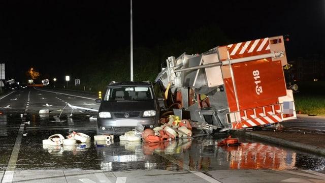 Gekippter Feuerwehrlastwagen liegt neben Privatauto, die Strasse ist nass, es liegen Schläuche umher.