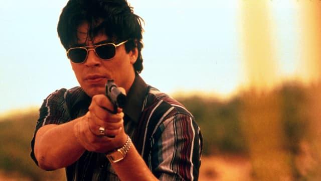 """Bild aus dem Film """"Traffic"""": Benicio del Toro steht in der Natur, trägt eine dunkle Sonnenbrille und zielt mit einer Pistole auf ein Tiel etwas unterhalb der Kamera."""