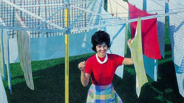 Eine Frau im Look der 50er hängt Wäsche auf.