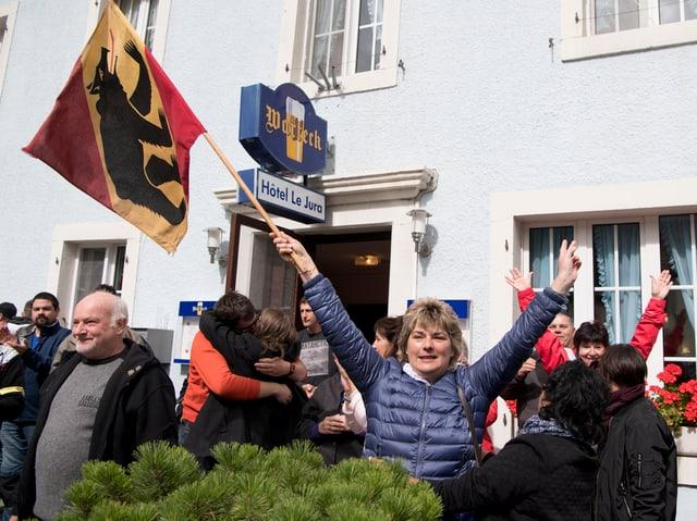 Eine Frau schwingt eine Berner Fahne.