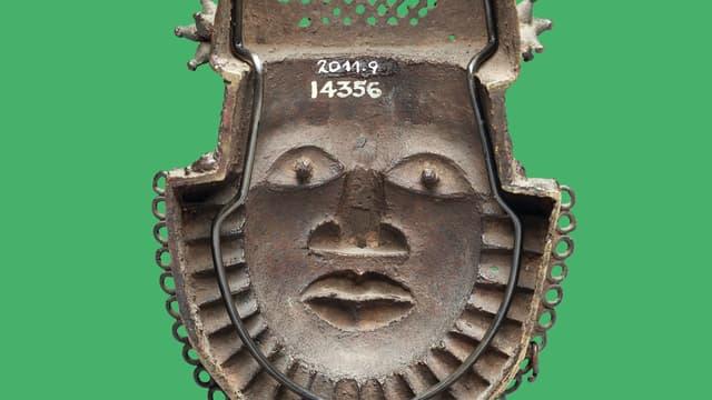 Eine Maske aus grauem Material. Sie zeigt ein Gesicht mit einer Art Bart.