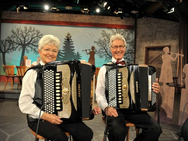 Ein älteres Ehepaar, das Akkordeon spielt.