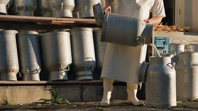 Mann schüttet Milch von einer Kanne in die andere