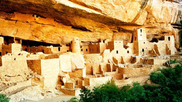Prähistorische Bauten unter einem Felsvorsprung.