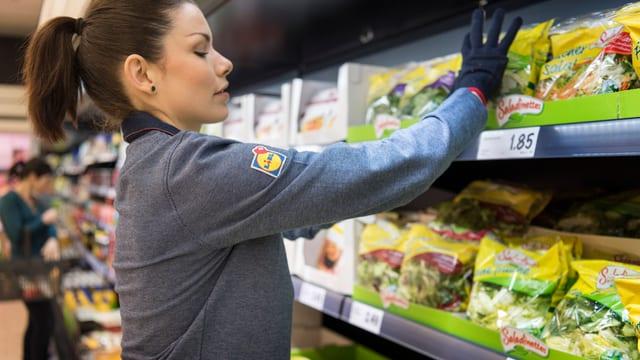 Frau füllt Regale in einem Supermarkt
