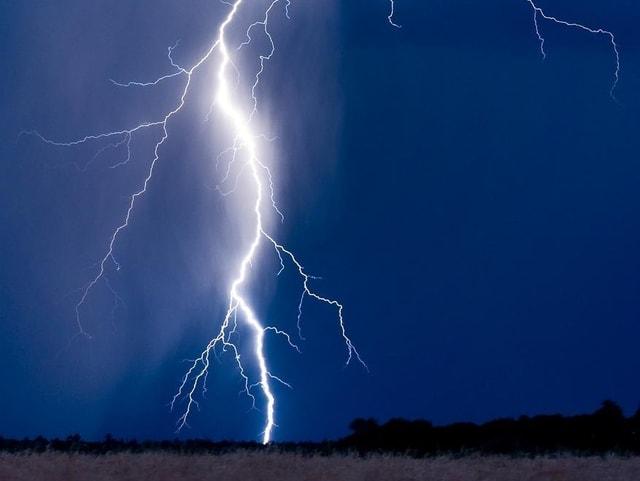 Ein nächtlicher Blitz schlägt in den Boden ein.