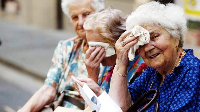Drei Seniorinnen auf einer Parkbank. Zwei wischen sich die schweissnasse Stirn mit einem Taschentuch.