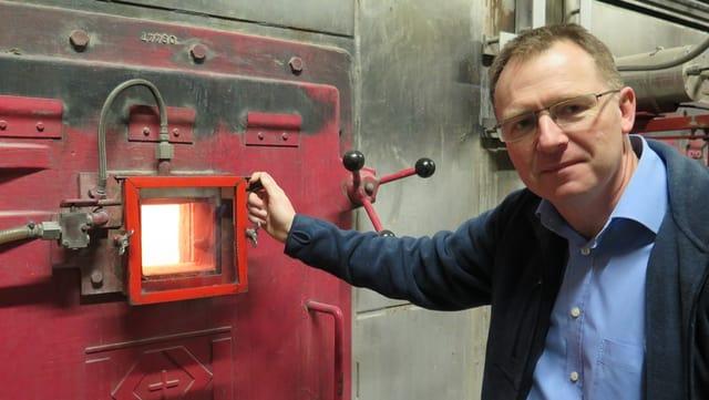 Hartmann steht rechts neben einem kleinen Fenster, durch das man in den Ofen und ins Feuer sieht.