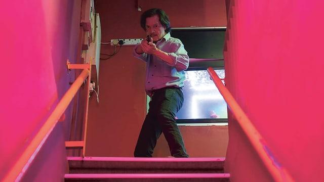 Filmszene: Mann mit Pistole steht oben an einer Treppe.
