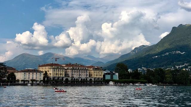Blick über den See auf Lugano, dahinter dicke Quellwolken.