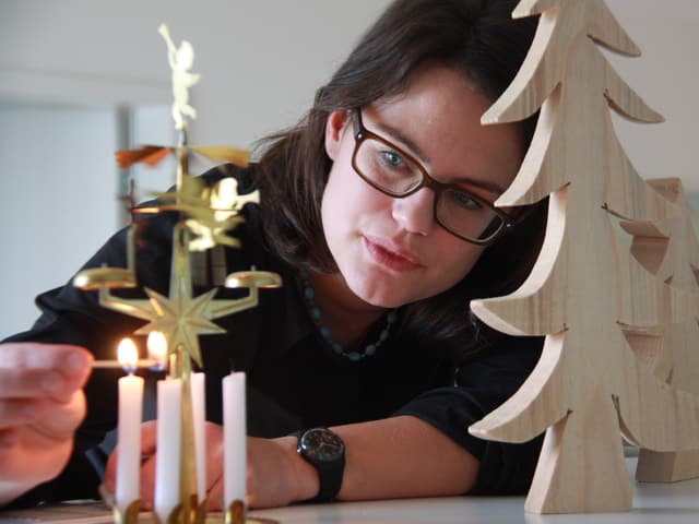 Fränzi Haller zündet eine der vier Kerzen an, die unter goldenen Engeln stehen.