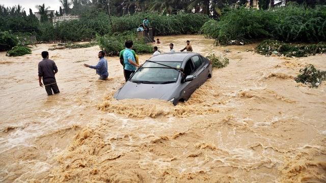Ein Auto und mehrere Menschen stehen im Hochwasser in Karachi.