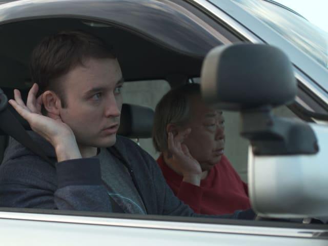 Zwei Männer in einem Auto, die eine Hand an ihr Ohr halten.