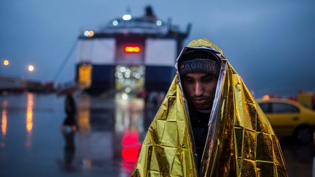 Ein Mann vor einer Fähre wärmt sich mit einer Kälteschutzdecke.