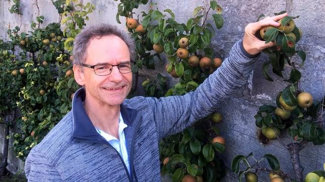 ein Mann steht in einem Garten und hält eine Frucht hoch
