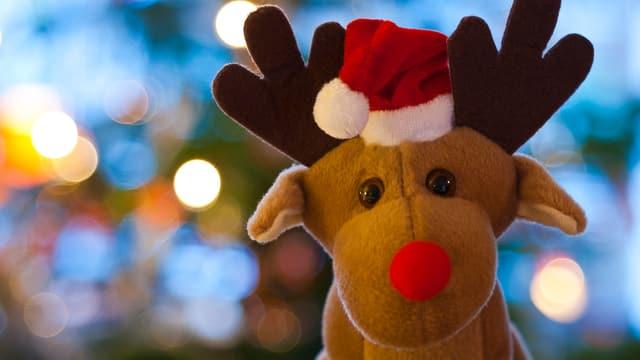 Ein Rentier aus Plüsch mit roter Nase und Weihnachtsmütze.