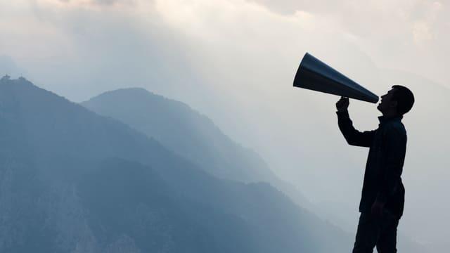 Ein Mann mit einem Megaphone in den Bergen.