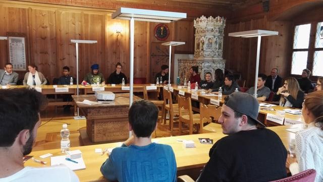 Sessiun dal parlament da giuventetgna da la citad da Cuira - ina sala da lain cun maisas en furma da U