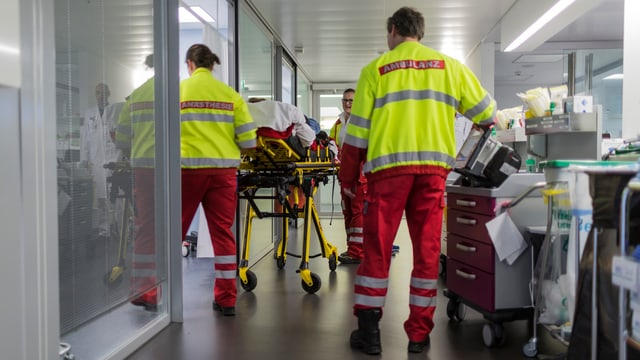 Partiziun d'urgenza en in ospital cun impiegads d'ambulanza.