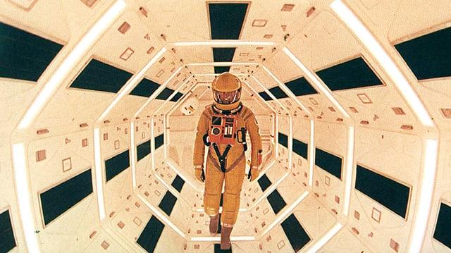Ein Mann in Raumanzug schreitet durch einen futuristischen Gang.