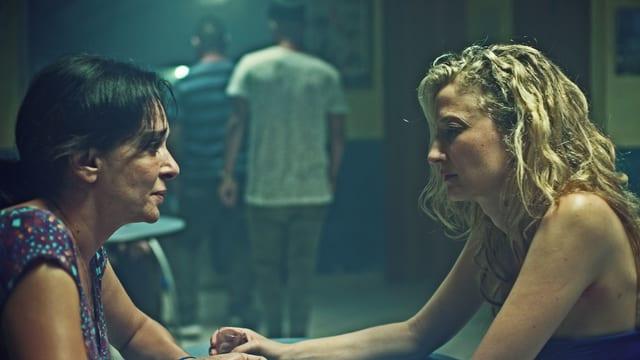 Zwei Frauen sitzen sich in einer Bar gegenüber. Die eine schaut der anderen in die Augen, diese schaut auf den Tisch.