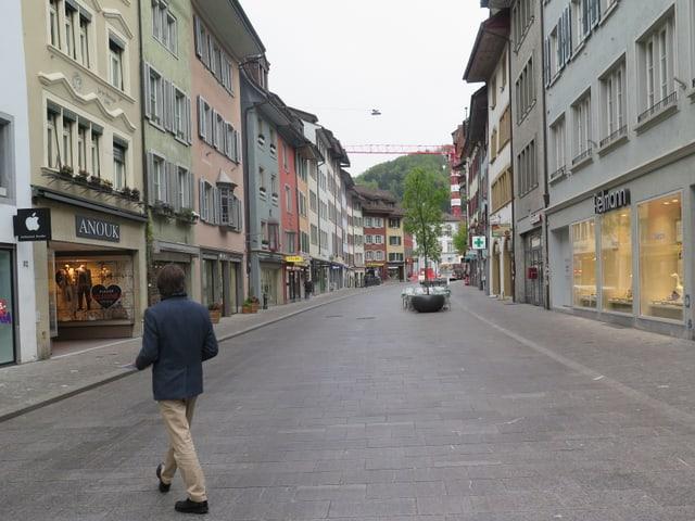 Eine Strasse in einer Stadt. Links und rechts sind Geschäfte.