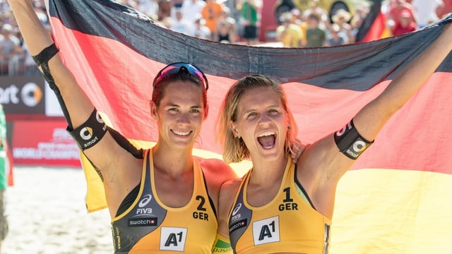 Kira Walkenhorst (san.) e Laura Ludwig che tegna ad aut la bandiera tudestga.