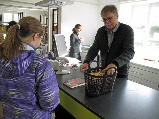 Regierungsrat Franz Enderli bedient eine junge Kundin in der Bibliothek.
