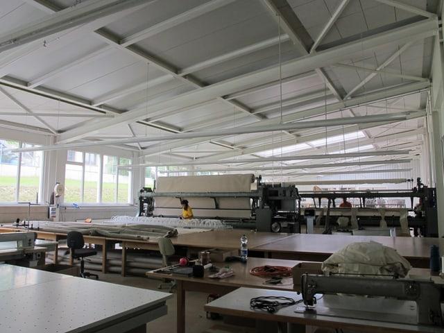 Blick in die Fabrikhalle, im Hintergrund steht eine Maschine.