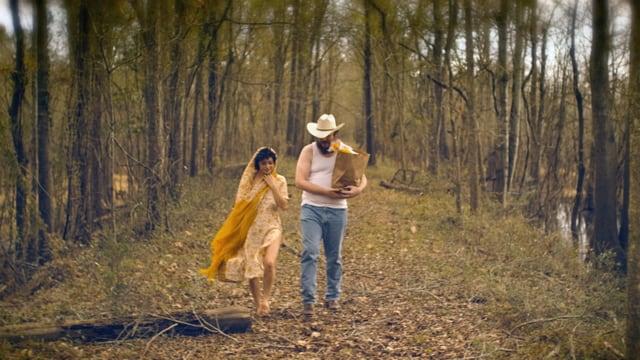 Ein Mann und eine Frau spazieren durch einen herbstlichen Wald